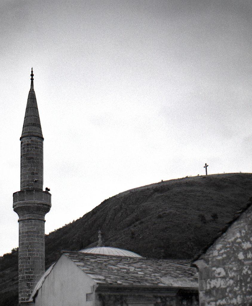 Cheveux au vent sur un minaret sous un regard christique